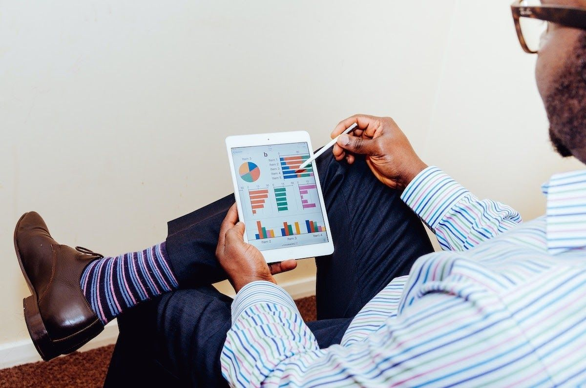 Person sitting with a tablet viewing a data visualization platform.